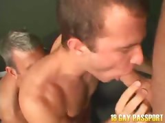Smiling young gay Corbin giving oral sex on his knees